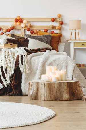 Lots of candles standing on a tree trunk next to a bed in a stylish bedroom Stock Photo