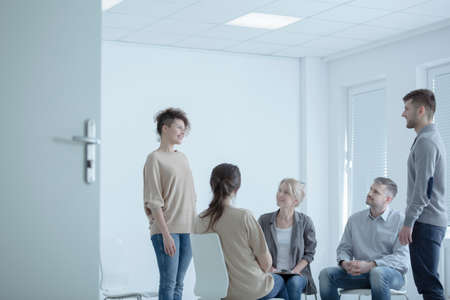 Woman standing in front of a man during marriage therapy with mediator in white office