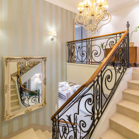 Beautiful staircase in victorian style with crystal chandelier and decorative railing