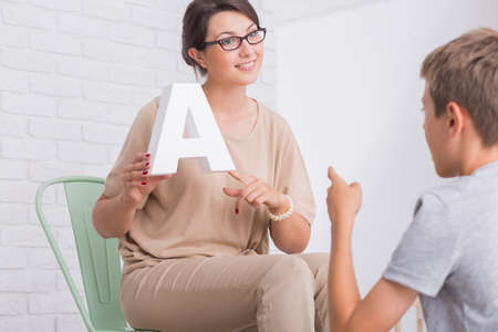 Young positive female speech and language therapist showing a letter to little boy during therapy session Stock Photo