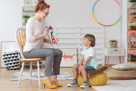 Happy little boy with pronunciation and language difficulties during speech therapy session with young female doctor Stock Photo