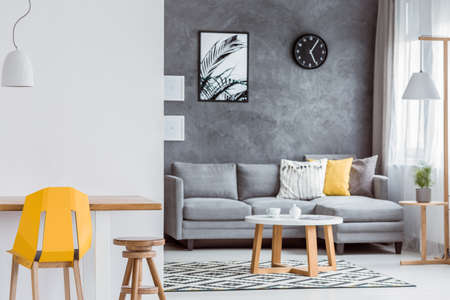 Modern interior design of open minimal living room with gray couch, textured wall, trendy accessories, yellow accents and wooden furniture
