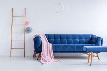 Roze sprei gegooid op de blauwe comfortabele bank in de kamer met houten ladder en lege witte muur