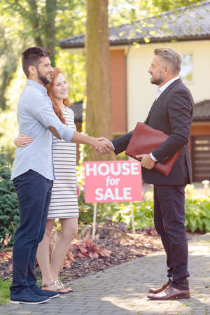 Real estate seller thanking young couple for coming to see home for sale