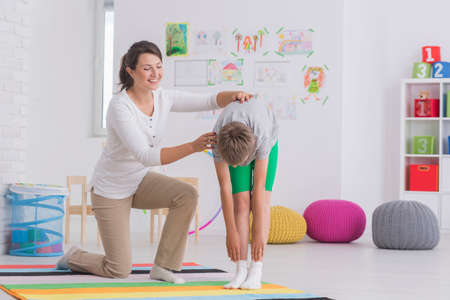 Young child physiotherapist working with little patient in pediatric spine clinic