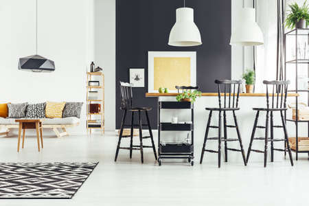 Shelf with crates next to kitchen with bar stools in open space with patterned pillows on sofa