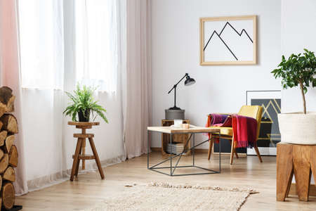 Apartment corner with mustard armchair with pink blanket laying on it, an end table,plants and pictures