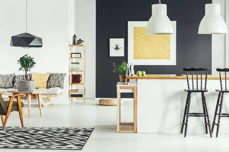 Geräumiges Retro- Wohnzimmer mit weißen Lampen über Kücheninsel mit rustikaler Barhocker Standard-Bild - 91210698