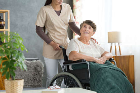 Nurse supporting happy elderly woman in wheelchair with green blanket on legs in nursing home
