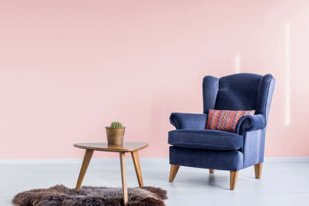 Wooden table with fresh potted plant standing on furry rug in pink waiting room with navy blue armchair