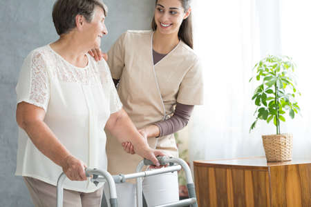 Smiling nurse in uniform helping old lady with walker during visit at home