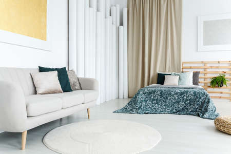Round white rug on the floor in feminine room with bed with floral blanket and sofa with decorative cushions