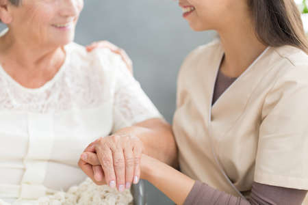 Close-up of happy family member holding hand of grandmother during meeting at home