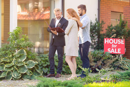 Real estate agent walking with married couple around block of flats for sale