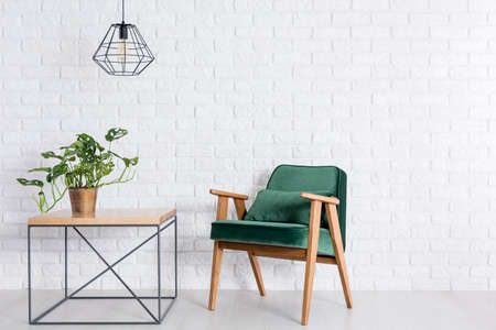 Room with empty white brick wall, green armchair and plant in copper pot Stockfoto