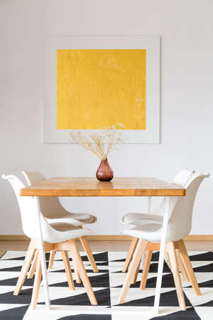 Flower in a red pot standing on the wooden surface of a long table with a set of four white chairs and a gold oil painting hanging above them