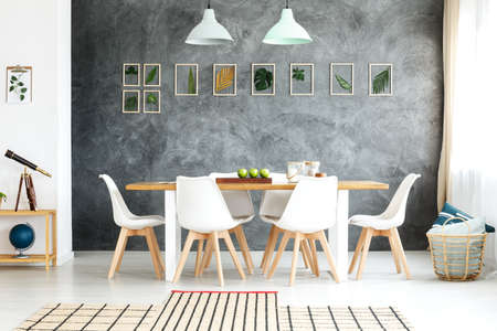 Wooden table and chairs in cozy dining space inspired by nature with jute rug, wicker basket and framed tropical leaves