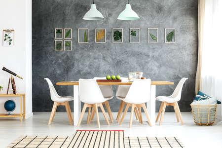 Houten tafel en stoelen in een gezellige eetkamer geïnspireerd op de natuur met jute tapijt, rieten mand en ingelijst tropische bladeren