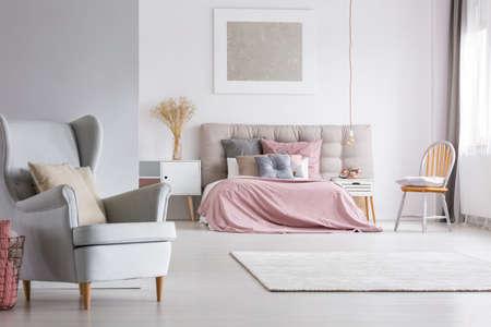 트렌디 한 안락 의자, 안락한 넓은 인테리어, 밝은 파스텔 침실, 스칸디나비아 가구, 핑크 퀼트 및 회색 침구 구비