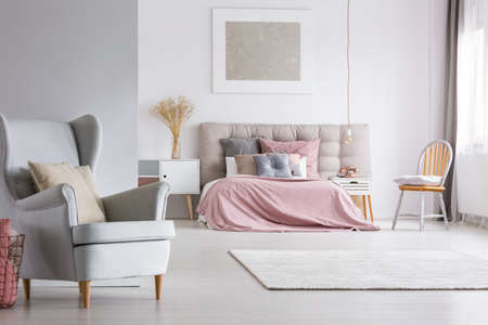 Trendy armchair in cozy spacious interior of light pastel bedroom with scandinavian furniture, pink quilt and gray bedhead Banco de Imagens