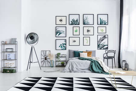 Posters on the wall above bed with green blanket in spacious bedroom with industrial furniture and geometric carpet