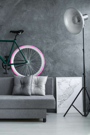 Designer lamp near grey sofa with pillows and bike on concrete wall in monochromatic living room with white poster