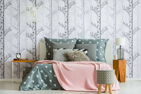 Designer stool in front of king-size bed with pink blanket in bedroom with lamp on wooden table