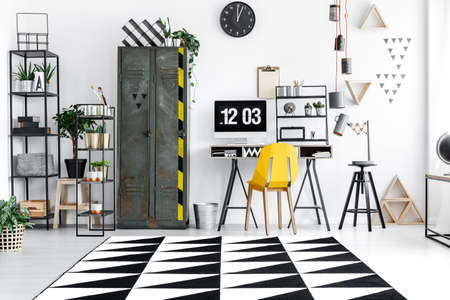 Bright home office room with industrial furniture, carpet and plants in pots