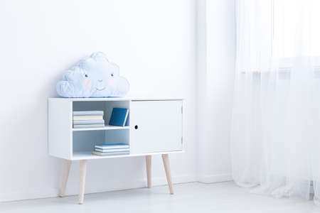 White scandi cupboard with books and pastel blue pillow in white room Stock Photo