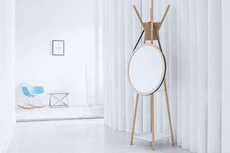 Mirror on wooden hanger against designer screen in minimalist interior with blue rocking chair
