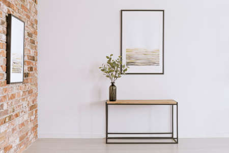 Simple poster on white wall above table with plant in black vase in art gallery 스톡 콘텐츠
