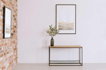 cartel simple en la pared blanca por encima de la mesa con la planta en florero negro en la galería de arte