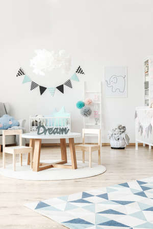 Elegant interior of a childs room containing modern trendy furniture, like a white cradle, and a small wooden table with a set of two chairs Stock Photo