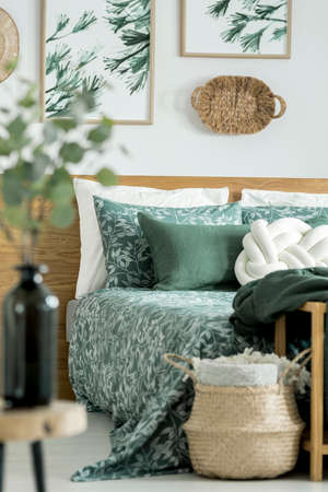 Basket next to bed with green blanket and pillows in bedroom with floral motif