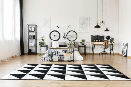 Geometrischer Teppich im geräumigen Schlafzimmer mit Fahrrad auf weißer Wand über Bett nahe Schreibtisch mit Stuhl