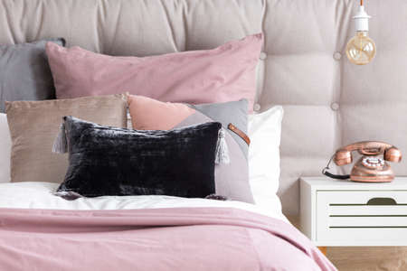 Metallic copper phone on white nightstand and bulb light in retro interior of stylish bedroom with pink linen and velour pillow