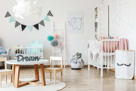 Small wooden table standing on a white carpet in a child room interior