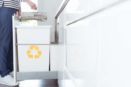 Close-up of eco friendly person sorting paper in the kitchen into recycling container marked with yellow symbol
