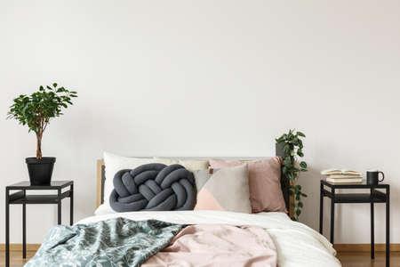 Oreiller de noeud, couverture verte et rose sur le lit dans une chambre simple et lumineuse avec une plante, des livres et une tasse sur une armoire
