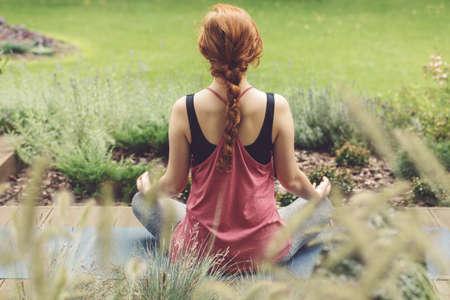 Starke Frau, die mit den gekreuzten Beinen auf Yogamatte auf Terrasse sitzt Lizenzfreie Bilder