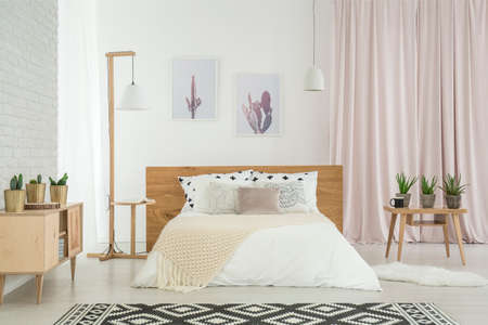 Bright feminine bedroom with cactus motif and king-size bed with cushions