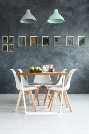 Wooden table styling with simple natural decorations in dining room with handmade botanical on gray textured wall
