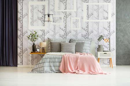 Pflanze, Lampe und Uhr auf Nachttisch neben Kingsize-Bett mit rosa Decke im Designer-Schlafzimmer Lizenzfreie Bilder