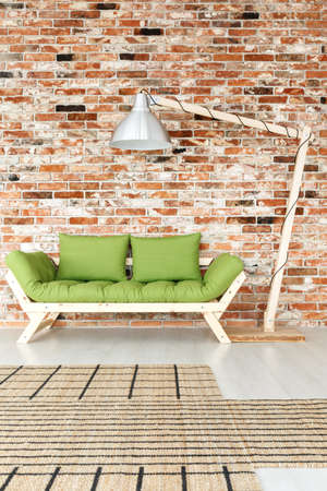 Large floor lamp next to wooden green couch in bright industrial interior with asymmetric patterned rug and brick wall