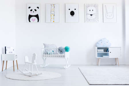 White rocking horse on carpet in babys bedroom with cupboard and white cradle with pompons