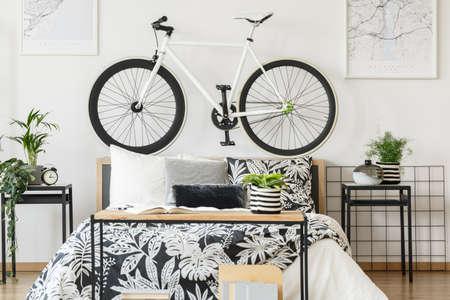 Weißes Fahrrad auf Bettkopf und Pflanzen auf Schränken im hellen Schlafzimmer des Teenagers mit Buch, Uhr und Vase