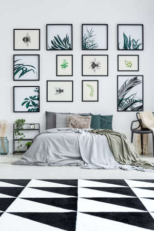 Gallery of floral posters above king-size bed in spacious bedroom with black and white carpet