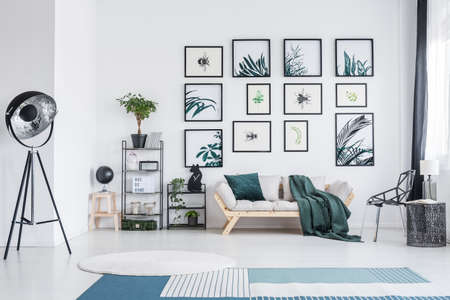 Blauer und weißer Teppich und Sofa im Wohnzimmer mit Metallmöbeln wie Lampe, Tisch, Stuhl und Regalen