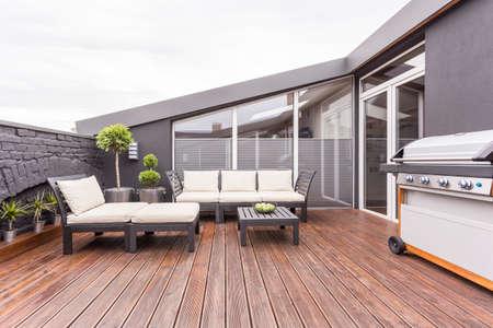 Móveis de jardim brilhantes, churrasqueira e plantas no aconchegante terraço com piso de madeira e parede de tijolos