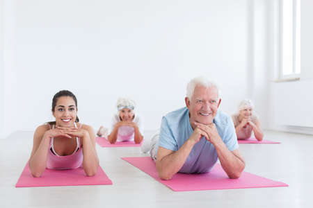 Group of seniors and young yoga instructor cooling down after exercising Stock Photo